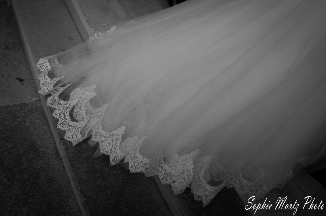 Photo en noir et blanc de détail robe de mariée, train dans les escaliers