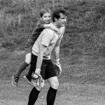photo d'un père et son fils sur les épaules en train de jouer au foot