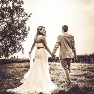 mariés dans un champ, photo en sépia très contrastée