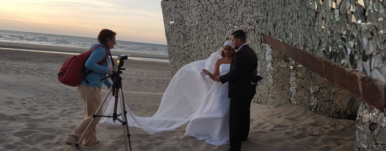 Shooting maries sur la plage de Dunkerque, photographe en train de guider ses mariés