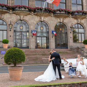 mariés qui s'embrassent devant leur mairie et leurs demoiselles d'honneur qui courent, Cadillac en arrière plan