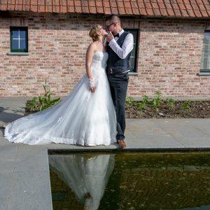 Couple de mariés au bord de piscine avec leur reflet dans l'eau