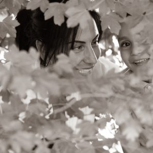 Photo de famille en noir et blanc, mère enfant cache-cache dans les arbres
