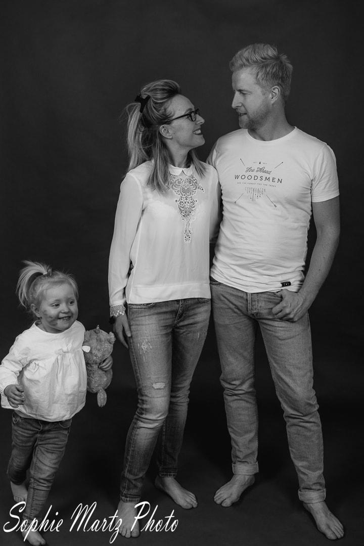 photo de famille en noir et blanc avec fille qui tourne autour de ses parents