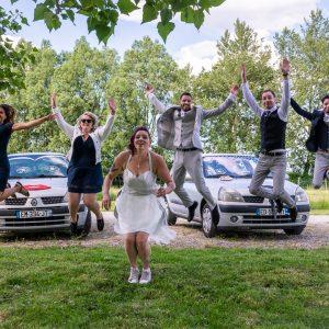Photo originale des mariés et leurs témoins avec leurs voitures en arrière plan
