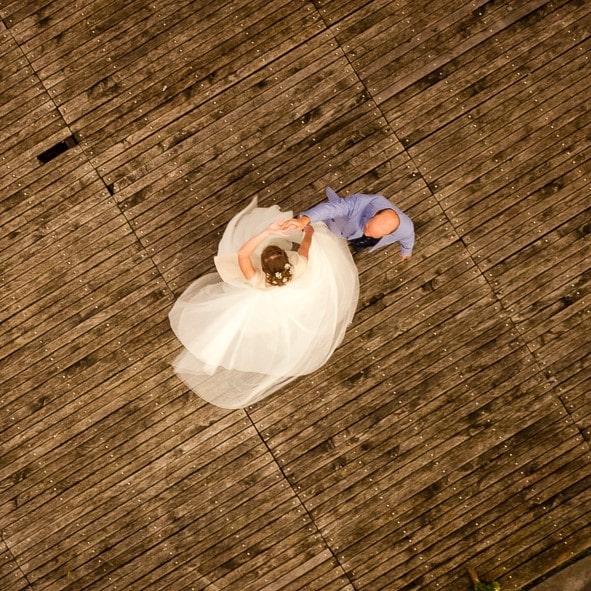 Photo de mariés prise au drone, robe de mariée qui vole