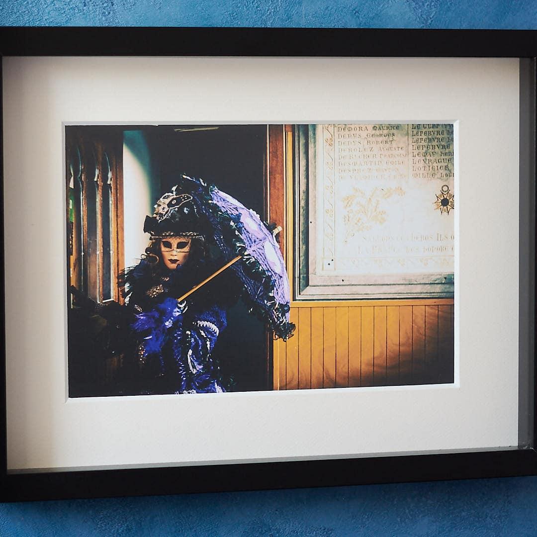 photo d'une femme en costume vénitien violet, encadrée dans une caisse américaine noire vitrée