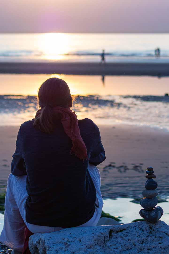 Photo de coucher de soleil sur la plage du nord de la France avec des galets en équilibre