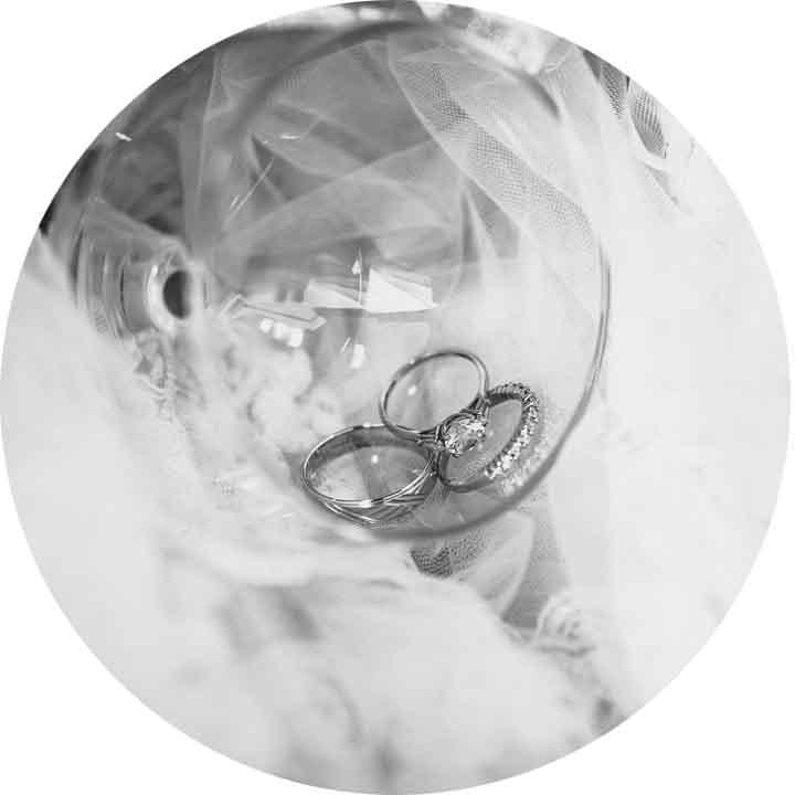 photo en noir et blanc des alliances dans un verre avec le voile de la mariée