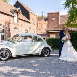 Photo de mariés en couleur, prise en aout. Mariés et leur voiture, une coccinelle blanche